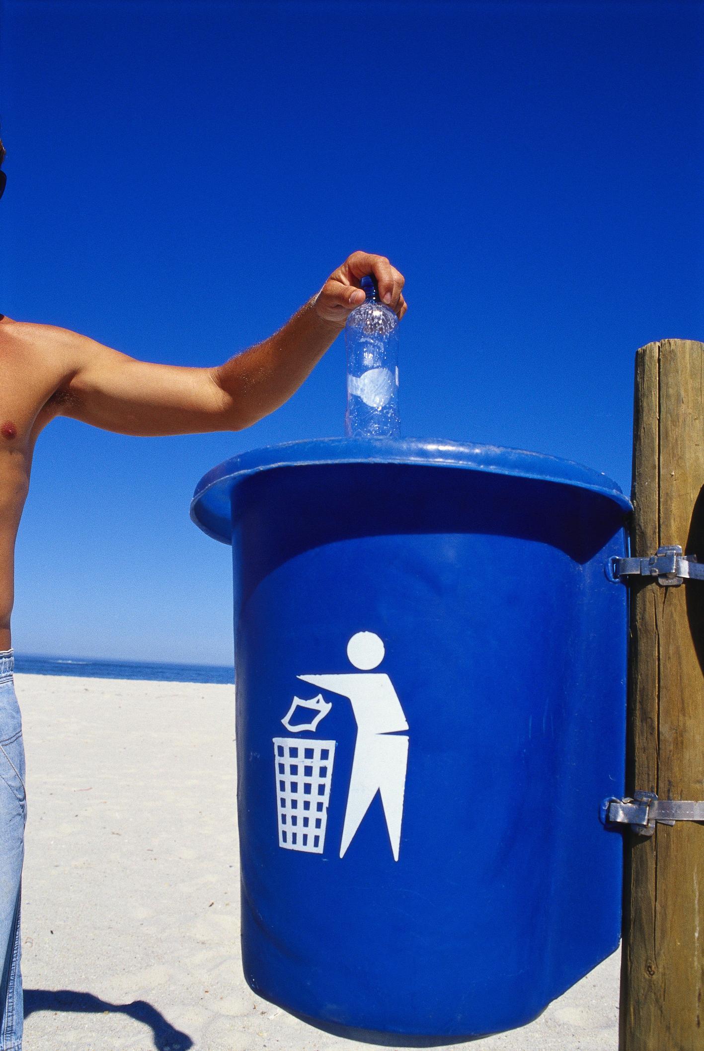Eine Person wirft eine Flasche in den Müll. Thema Verpackungsrecycling