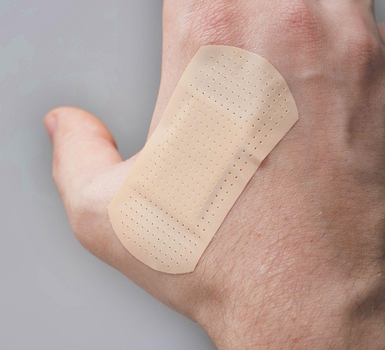 Ein Pflaster klebt auf einer Hand. Thema: Verpackung in der Medizintechnik