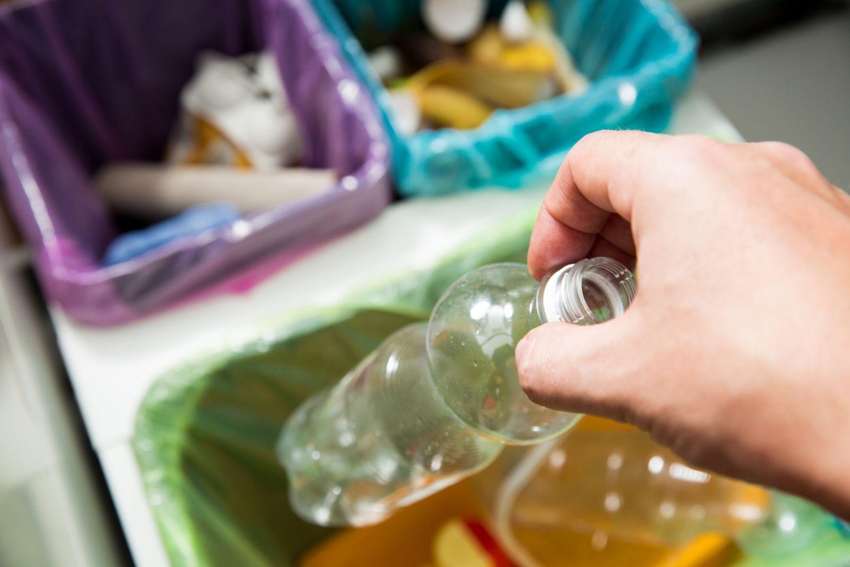 Jemand wirft eine Kunststoffflasche in den Müll. Thema Biokunststoffe