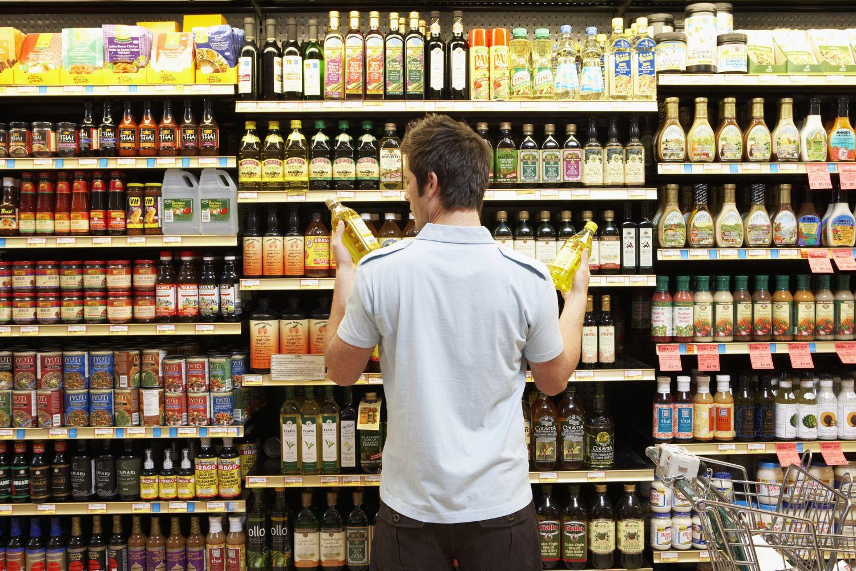 Ein Mann steht vor einem Supermarktregal. Thema Lebensmittelverpackung