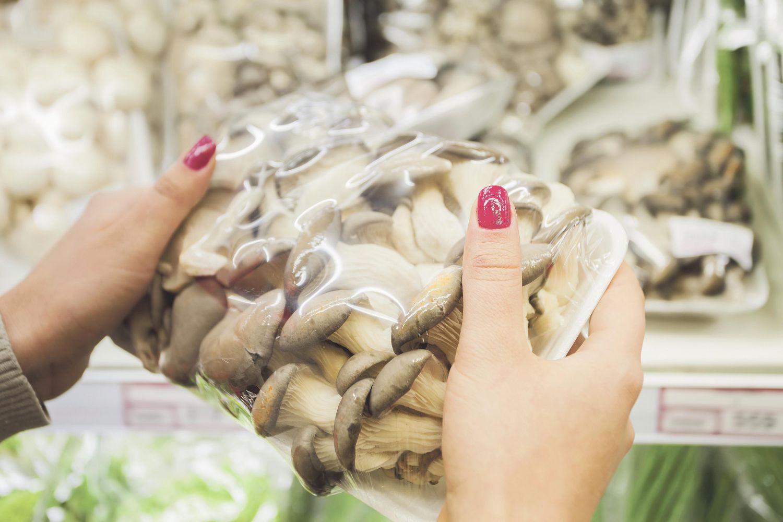 Eine Kundin hält verpackte Pilze in den Händen. Thema: Lebensmittelverpackungen