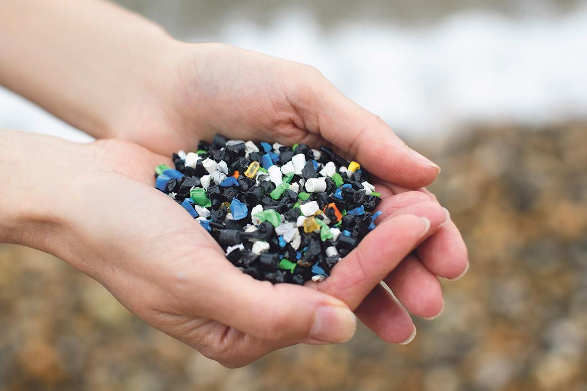 Hände, die Kunststoffperlen halten