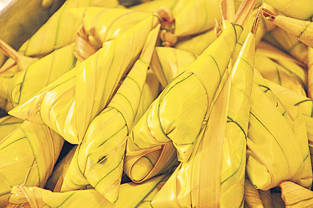 Palmenblätter umhüllen Klebreis. Thema: flexible Verpackung