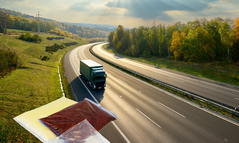 Ein LKW auf der Autobahn. Im Vordergrund sind zwei Verpackungen für Flüssigkeiten zu sehen.