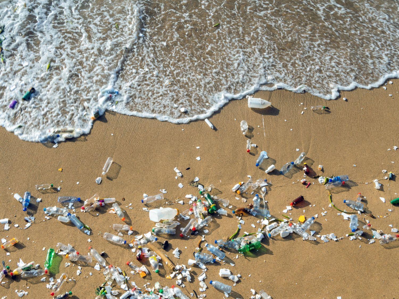 Wellen schieben Plastikmüll an den Strand