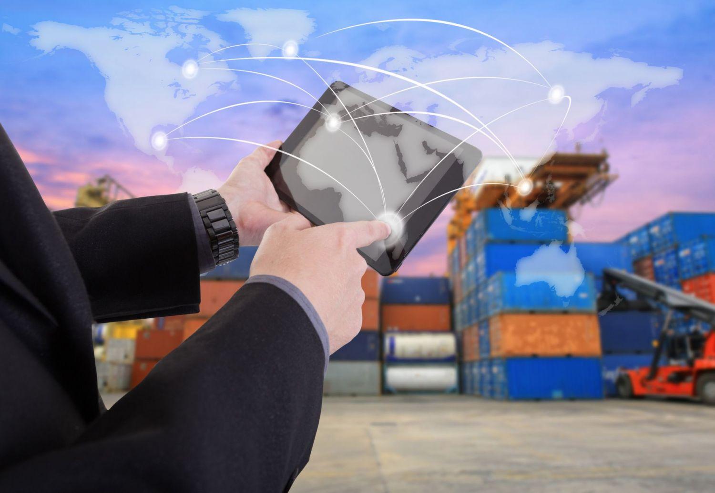 Eine Person tippt etwas in ein Tablet ein. Im Hintergrund sind Container zu sehen. Thema: intelligente Verpackung