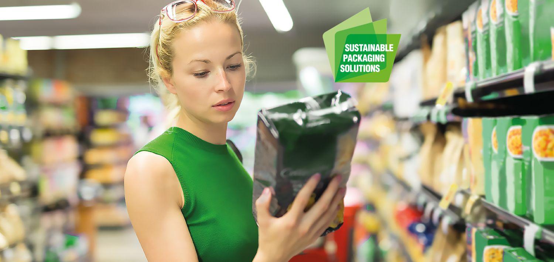 Eine Frau steht im Supermarkt und schaut sich eine Verpackung an.