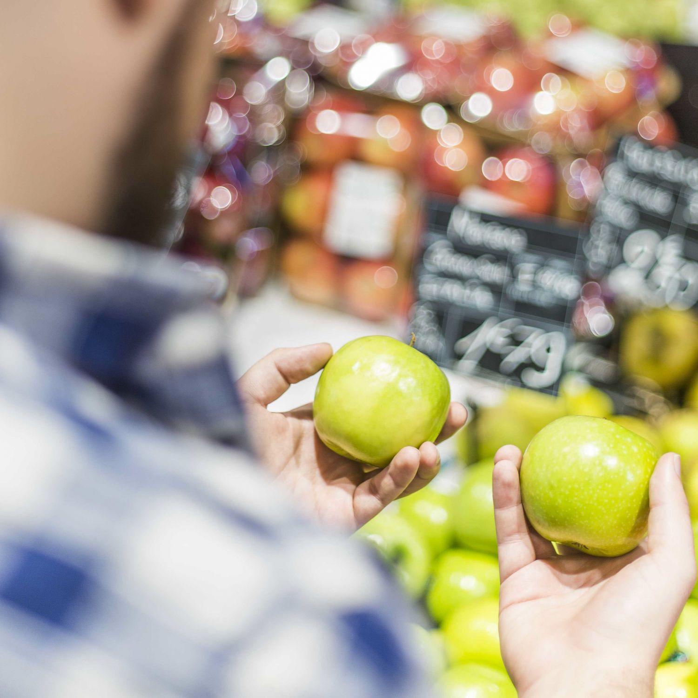 Ein Kunde hält zwei grüne Äpfel in seinen Händen. Thema: Verpackungsmaterialien