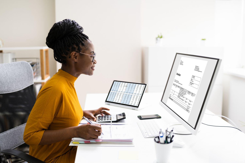 Eine Frau, die an mehreren Bildschirmen arbeitet.