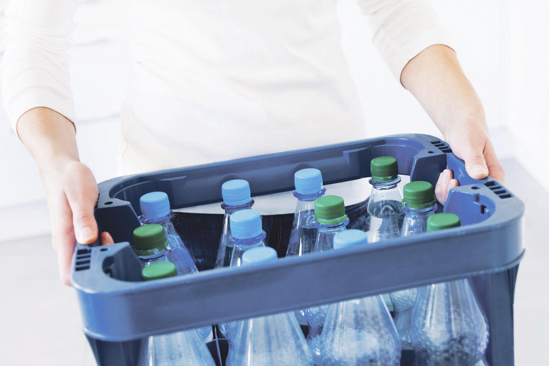 Ein Mann trägt eine Kiste mit Mehrwegflaschen. Thema: Das deutsche Mehrwegsystem